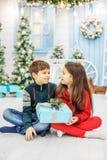 Regali aperti della sorella e del fratello Il ragazzo e la ragazza Concetto nuovo Fotografia Stock