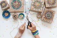 Regali avvolti in carta kraft Sulle scatole modello dipinto della mandala Fotografie Stock