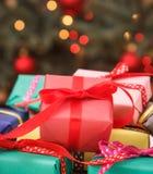 Regali avvolti variopinti ed albero di Natale con le luci nel fondo fotografia stock libera da diritti