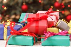 Regali avvolti variopinti ed albero di Natale con le luci nel fondo fotografie stock libere da diritti