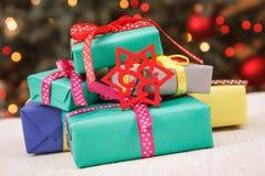 Regali avvolti variopinti ed albero di Natale con le luci nel fondo, concetto festivo di tempo fotografie stock libere da diritti