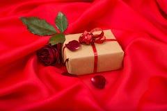 Regali con la rosa rossa su raso rosso Immagini Stock