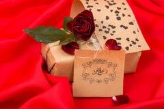 Regali con la rosa rossa su raso rosso Fotografia Stock Libera da Diritti