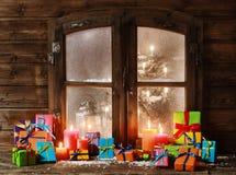 Regali di Natale assortiti e candele alla finestra Fotografie Stock