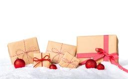 Regali di Natale avvolti in carta marrone con il nastro rosso ed in neve su fondo bianco fotografia stock libera da diritti