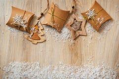 Regali di Natale in carta kraft con giocattoli casalinghi con neve Fotografia Stock Libera da Diritti