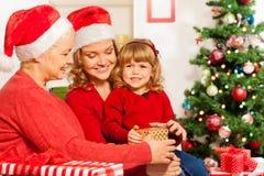 Regali di Natale che si aprono la vigilia dei nuovi anni Fotografie Stock Libere da Diritti