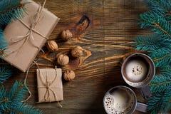Regali di Natale con due tazze di cappuccino, dei dadi, dei coni e del ramo dell'abete sulla fine di legno del fondo su Fotografie Stock