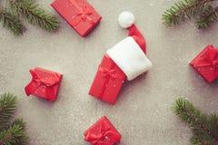 Regali di Natale con il cappello di Santa ed i rami attillati naturali Fotografia Stock