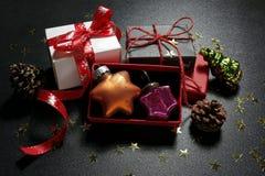 Regali di Natale con le bagattelle, i coni e le stelle d'oro di lustro Fotografia Stock