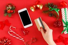 Regali di Natale d'acquisto della ragazza online sullo smartphone con la carta di credito Fotografie Stock Libere da Diritti