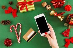 Regali di Natale d'acquisto della ragazza online sullo smartphone con la carta di credito Immagini Stock