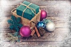 Regali di Natale decorati con cavo di tela, cannella, pigne, decorazione di Natale Immagine tonificata Neve e raggi disegnati Fotografia Stock