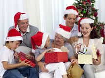 Regali di Natale di apertura della famiglia nel paese Fotografie Stock Libere da Diritti