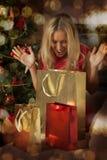 Regali di Natale di apertura della giovane donna Fotografia Stock Libera da Diritti