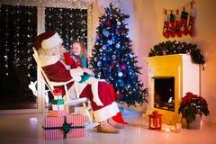 Regali di Natale di apertura di Santa e dei bambini Immagine Stock