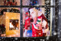 Regali di Natale di apertura di Santa e dei bambini Fotografia Stock Libera da Diritti