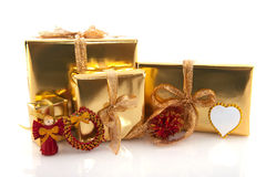 Regali di Natale dorati con gli ornamenti rossi Fotografie Stock