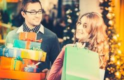 Regali di Natale e borse di acquisto delle coppie in centro commerciale Fotografie Stock Libere da Diritti