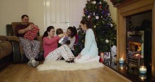 Regali di Natale felici di apertura della famiglia a casa vicino all'albero di Natale La figlia ha offerto un regalo a suo padre  stock footage