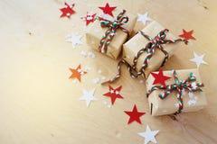 Regali di Natale in Kraft ad ingrassare un fondo di legno fotografie stock libere da diritti