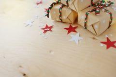 Regali di Natale in Kraft ad ingrassare un fondo di legno immagine stock libera da diritti