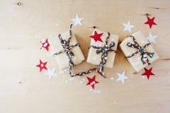 Regali di Natale in Kraft ad ingrassare un fondo di legno immagini stock libere da diritti