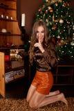 Regali di Natale nascondentesi della bella donna mentre facendo un silenzio Fotografie Stock Libere da Diritti
