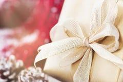 Regali di Natale o regali con le decorazioni eleganti di natale e dell'arco su fondo nevoso luminoso Immagini Stock