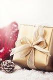 Regali di Natale o regali con le decorazioni eleganti di natale e dell'arco su fondo nevoso luminoso Fotografia Stock