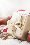 Regali di Natale o regali con le decorazioni eleganti di natale e dell'arco su fondo nevoso luminoso Immagine Stock