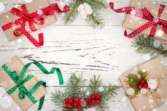 Regali di Natale in scatole su un fondo di legno con lo spazio della copia Immagine Stock