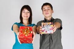 Regali di offerta dell'uomo e della ragazza alla macchina fotografica Immagini Stock