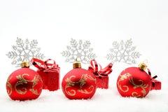 Regali e bagattelle rossi di natale con i fiocchi di neve su neve immagini stock libere da diritti