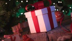 Regali ed ornamenti di Natale sul bokeh di legno delle luci di Natale della tavola stock footage
