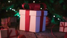 Regali ed ornamenti di Natale sul bokeh di legno delle luci di Natale della tavola archivi video