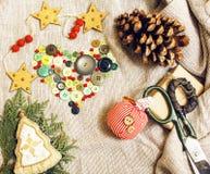 Regali fatti a mano di natale nel disordine con i giocattoli, candele, abete, annata di legno del nastro Immagine Stock