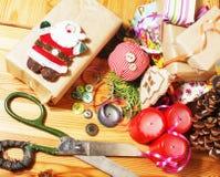 Regali fatti a mano di natale nel disordine con i giocattoli, candele, abete, annata di legno del nastro Fotografia Stock Libera da Diritti
