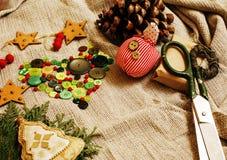 Regali fatti a mano di natale nel disordine con i giocattoli, candele, abete, annata di legno del nastro Fotografie Stock