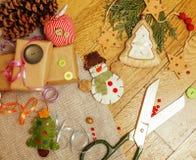 Regali fatti a mano di natale nel disordine con i giocattoli, candele, abete, nastro, annata di legno del cono dell'albero, vista Fotografia Stock