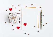 Regali fatti a mano rustici e una lettera su fondo bianco decorato con i cuori ed i chicchi di caffè Vista superiore, disposizion Fotografia Stock