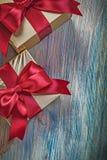 Regali inscatolati con gli archi rossi sulla celebrazione d'annata co del bordo di legno Immagine Stock