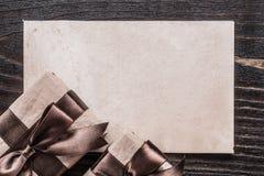 Regali inscatolati con la carta legata dei nastri sul bordo di legno Fotografia Stock
