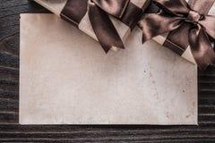 Regali inscatolati con la carta marrone legata dei nastri sul bordo di legno Fotografia Stock