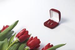 Regali per i cari Un mazzo dei tulipani rossi è sparso su una superficie bianca Vicino è un contenitore rosso di velluto con un a Immagine Stock