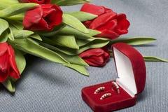 Regali per i cari Un mazzo dei tulipani rossi Vicino è un contenitore rosso di velluto con un anello e gli orecchini Immagini Stock Libere da Diritti