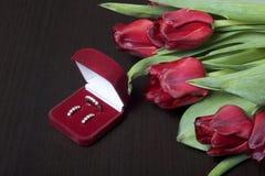 Regali per i cari Un mazzo dei tulipani rossi Vicino è un contenitore rosso di velluto con un anello e gli orecchini Immagini Stock
