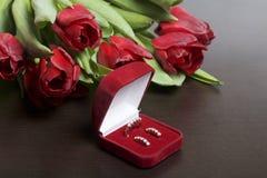 Regali per i cari Un mazzo dei tulipani rossi Vicino è un contenitore rosso di velluto con un anello e gli orecchini Immagine Stock Libera da Diritti