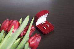 Regali per i cari Un mazzo dei tulipani rossi Vicino è un contenitore rosso di velluto con un anello e gli orecchini Fotografia Stock Libera da Diritti