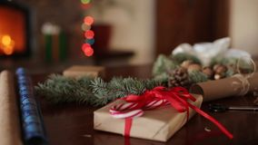 Regali, presente e materiali da imballaggio: carta da imballaggio, rami di albero dell'abete, coni e nastri sulla tavola camino archivi video